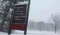 Calvin College sign with a wintery background.