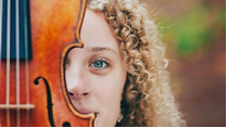 Half of a young woman's face peaks out from behind a violin, which is in the foreground.