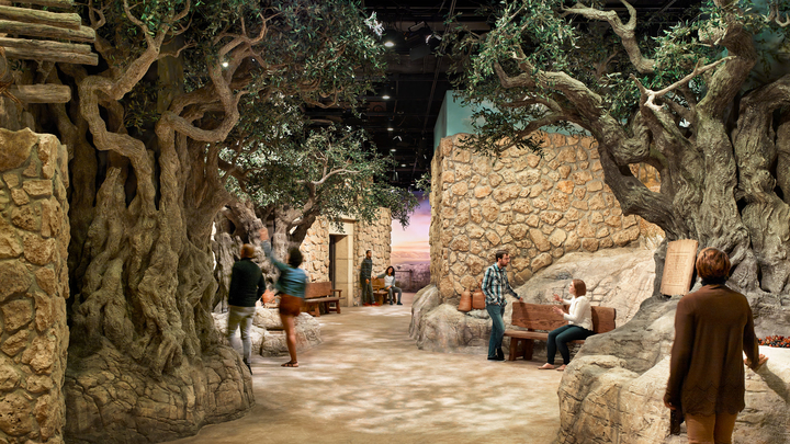 People explore a museum exhibit reconstruction of an ancient town.