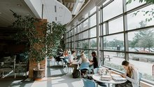 Students study at a few circular tables in an open space with lots of natural light.