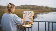 A woman stands painting on artboard at Reed's Lake.