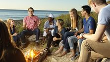 A guy in a red shirt shares a story with his friends around a campfire on the beach.