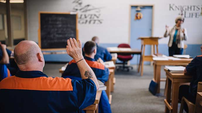 A Calvin Prison Initiative student in class, raising his hand from his desk.